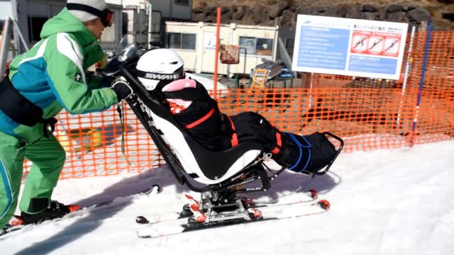 video footage taken at fujimi kogen snow resort in fujimi nagano prefecture shows volunteers at a feb 2324 event helping disabled children ski down... - insel honshu stock-videos und b-roll-filmmaterial