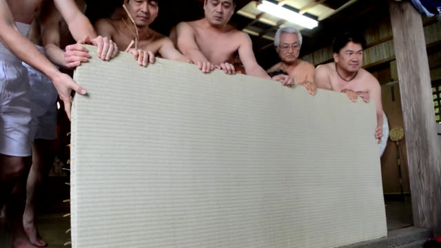 video footage taken at nankojinja shrine in isahaya nagasaki prefecture shows about 40 barechested parishioners roughly rubbing each other with straw... - 上半身裸点の映像素材/bロール
