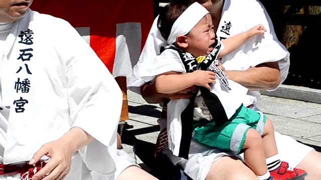 "video footage taken at toishihachimangu shrine in shunan yamaguchi prefecture shows bawling babies being passed beneath a ""mikoshi"" portable shrine... - health and safety点の映像素材/bロール"