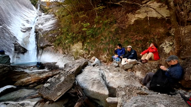 "video footage taken in nobeoka, miyazaki prefecture, shows hikers resting on ""pakkuniwa"" , a boulder that looks as it is agape and ready to swallow,... - boulder rock stock-videos und b-roll-filmmaterial"