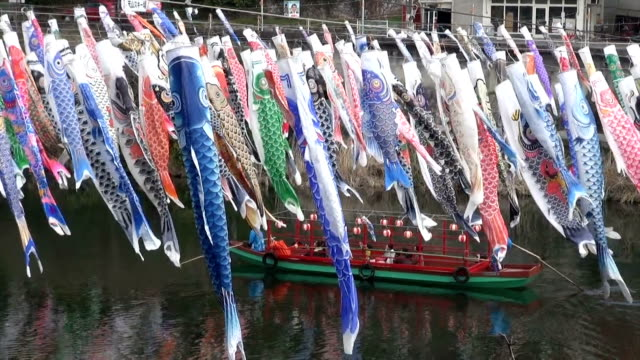 vídeos de stock, filmes e b-roll de video footage taken in yamato saga prefecture shows families boarding a small boat in order to sail under a display of about 300 colorful carpshaped... - biruta