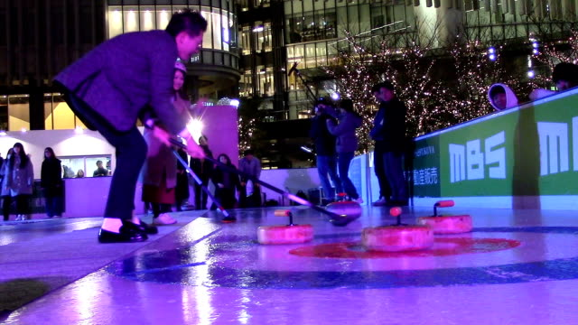 "Video footage taken on Feb 23 at an outdoor skating rink in the Umeda district of Osaka shows people trying the skills at a ""curling night"" event..."