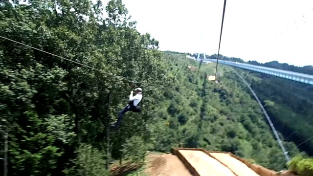 video footage taken on july 23 in mishima shizuoka prefecture shows adventurous visitors sliding along a wire strung beside the 400meterlong mishima... - 訪問点の映像素材/bロール