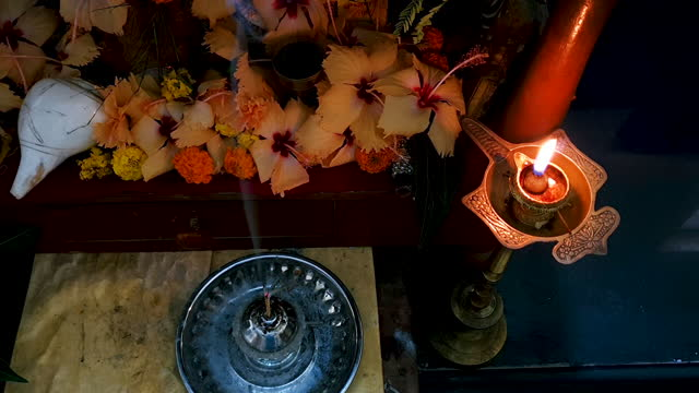 4k video from above of candle, burning joss sticks (incense sticks) with smoke, flowers (hibiscus) and holy conch at the place of worship - shrine stock videos & royalty-free footage