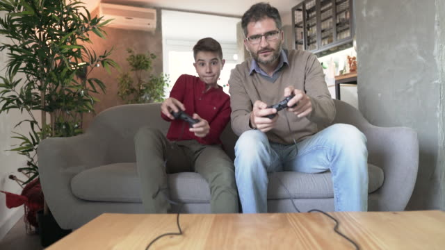 video games - son vs dad - leisure games stock videos & royalty-free footage