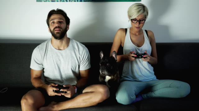 video gaming duel between couple - gioco d'azzardo video stock e b–roll