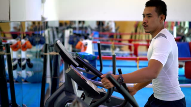 4k video : group of people using running machines at gym - cross trainer stock videos & royalty-free footage