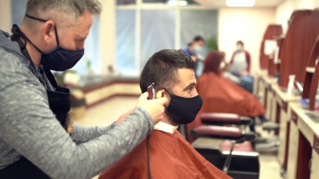 4k video hairdressers cutting hair with electric razor, during covid-19 - small business stock videos & royalty-free footage