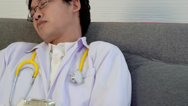 4 k ビデオ: 健康リスクはスリープ剥奪の概念、懸命に働かせた後ソファで寝て疲れ医師によって引き起こされます。 - きつい点の映像素材/bロール
