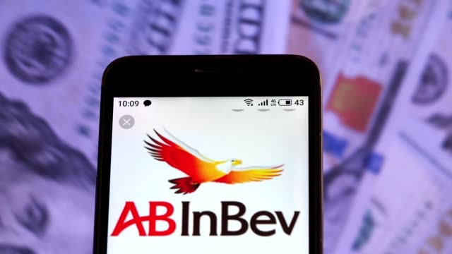 video illustration the logo of anheuserbusch inbev is displayed on a smartphone in hands counting 100 dollar bills video taken in kiev ukraine on... - anheuser busch inbev stock videos and b-roll footage
