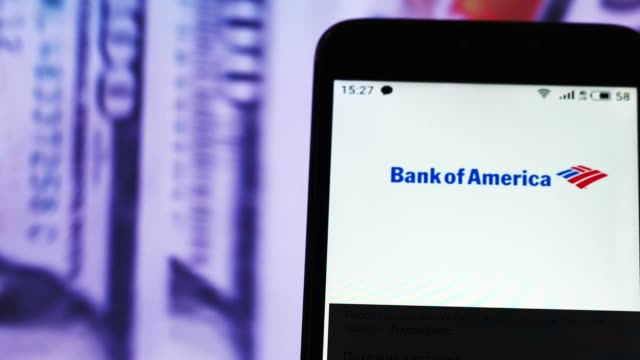 video illustration the logo of bank of america is displayed on a smartphone in hands counting 100 dollar bills video taken in kiev ukraine on tuesday... - bank of america stock videos & royalty-free footage