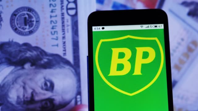 video illustration the logo of bp plc is displayed on a smartphone in hands counting 100 dollar bills video taken in kiev, ukraine, on thursday,... - plc stock videos & royalty-free footage