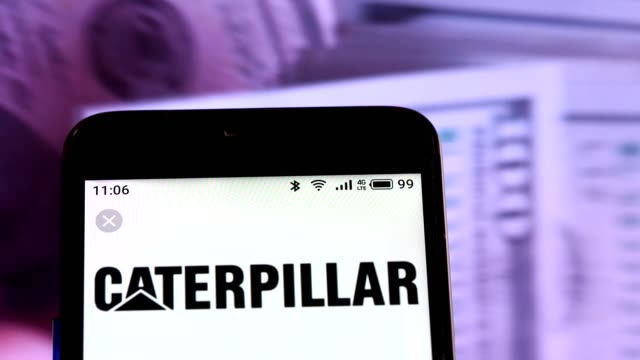 video illustration the logo of caterpillar inc is displayed on a smartphone in hands counting 100 dollar bills video taken in kiev ukraine on... - caterpillar inc video stock e b–roll