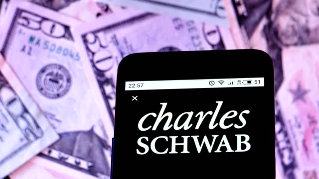 video illustration the logo of charles schwab corporation is displayed on a smartphone rotating at different denominations dollar bills video taken... - 人工物点の映像素材/bロール