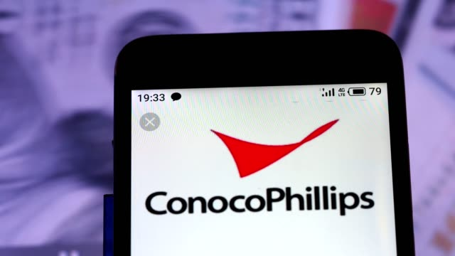 video illustration the logo of conocophillips is displayed on a smartphone in hands counting 100 dollar bills video taken in kiev ukraine on... - conocophillips stock videos & royalty-free footage