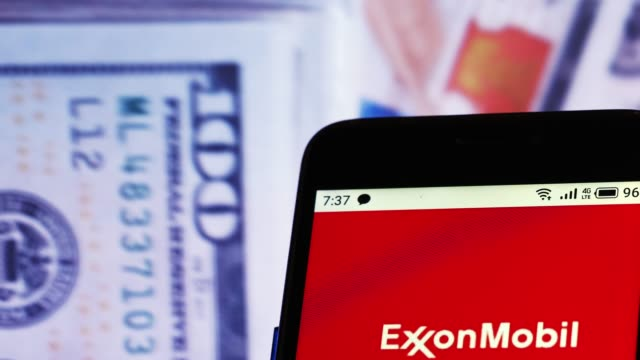 video illustration the logo of exxon mobil corporation is displayed on a smartphone in hands counting 100 dollar bills video taken in kiev ukraine on... - exxon stock videos & royalty-free footage