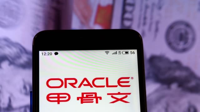 video illustration the logo of oracle corporation is displayed on a smartphone in hands counting 100 dollar bills video taken in kiev ukraine on... - oracle corporation stock-videos und b-roll-filmmaterial
