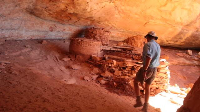 vídeos de stock e filmes b-roll de vídeo em hd homem explora antigas ruínas de pueblo utah - pueblo cultura tribal da américa do norte
