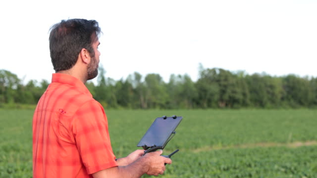 4K Video Man Farmer Pilot Using Drone Controller at Sunset