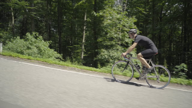 4k video man on racing bike cycling on road through forest - steil stock-videos und b-roll-filmmaterial
