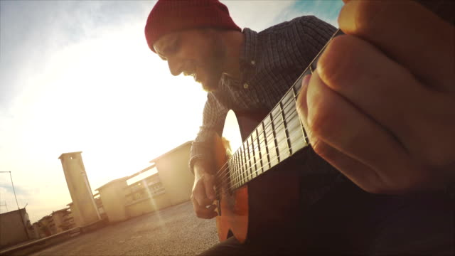 pov video: man playing guitar and singing - balcony stock videos & royalty-free footage