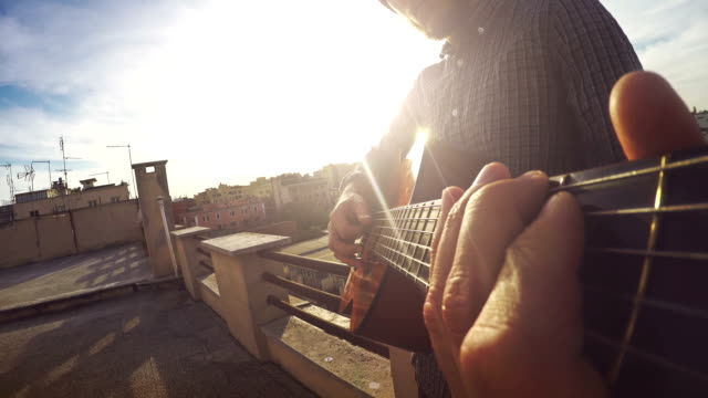 pov video: man playing guitar on the terrace - guitar stock videos & royalty-free footage