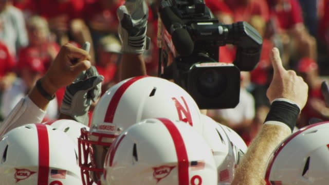 Video News Camera is hoisted overhead to shoot football players psyching up.