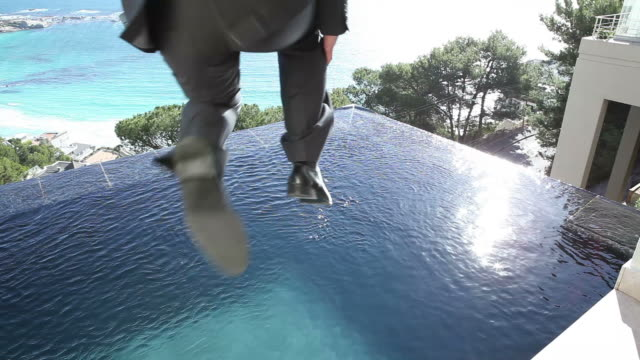 vídeos y material grabado en eventos de stock de video of a businessman jumping in a swimming pool - traje completo