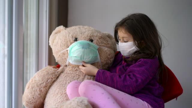 vídeos de stock, filmes e b-roll de 4k vídeo de uma menina bonita com máscara protetora ao lado da janela com seu ursinho de pelúcia - máscara cirúrgica