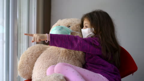 4k video of a cute little girl whit protective mask standing next to the window with her teddy bear - one girl only stock videos & royalty-free footage