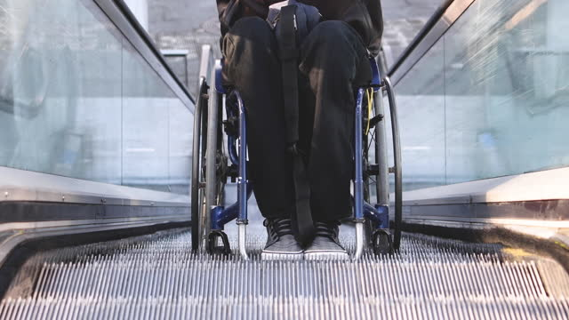 video of a handicapped man climbing up an escalator with his wheelchair. selective focus. - young men stock videos & royalty-free footage