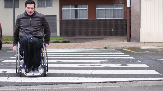 video of a handicapped man crossing a crosswalk with his wheelchair. - young men stock videos & royalty-free footage