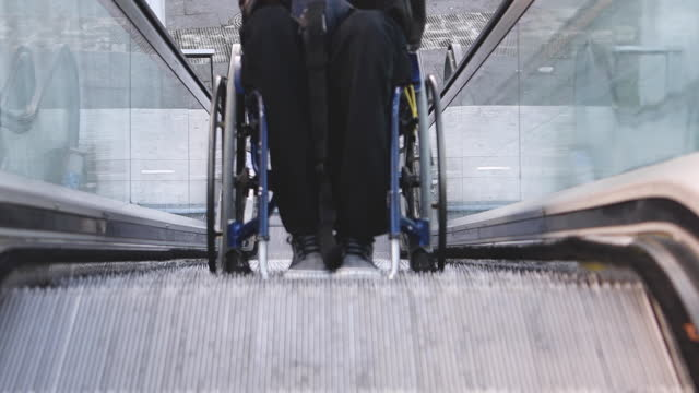video of a handicapped man finishing climbing an escalator with his wheelchair. selective focus. - young men stock videos & royalty-free footage