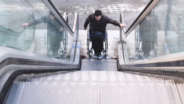 video of a handicapped man finishing his descent down an escalator with his wheelchair. - young men stock videos & royalty-free footage
