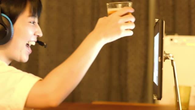 自宅でオンラインで飲む日本人女性の4kビデオ - ビール点の映像素材/bロール