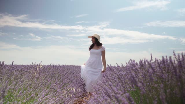 stockvideo's en b-roll-footage met video of a latina woman walking through the lavender, she turns around and smiles looking at the camera. - sunny