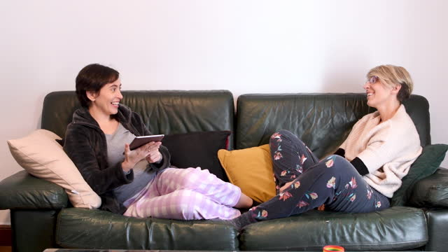 vídeos y material grabado en eventos de stock de video of a lesbian couple lying on the living room sofa in their pyjamas. one of them is looking at a tablet. - carrying