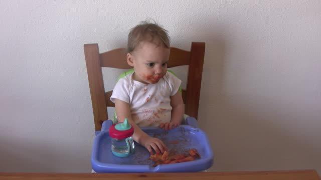 video di un ragazzino mangiare pasta - soltanto un neonato maschio video stock e b–roll