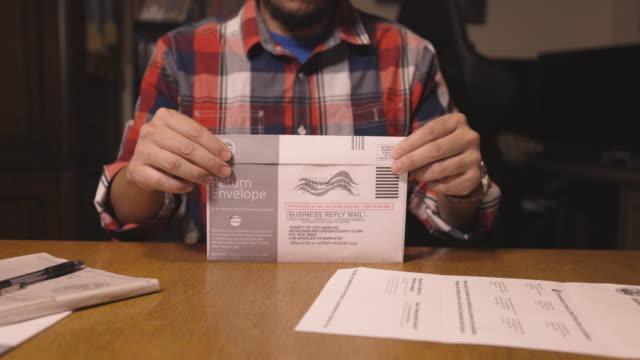4k video eines mannes, der ein wahlformular ausfüllt, um für eine wahl im jahr 2020 zu stimmen - wahlmöglichkeit stock-videos und b-roll-filmmaterial