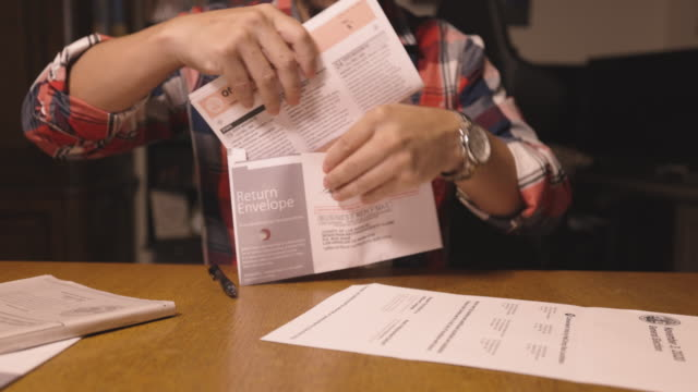 4k video of a man filling out a ballot form to vote for an election during 2020 - scheda di votazione video stock e b–roll