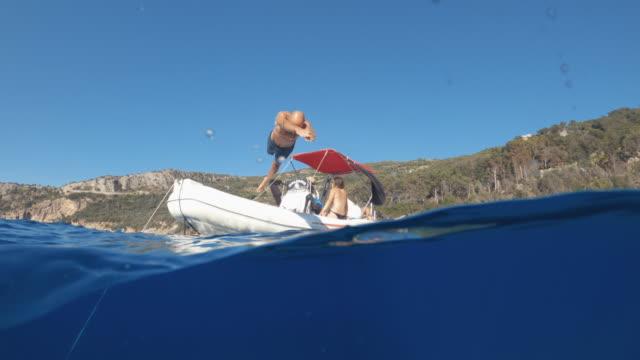 ボートから夏の海でジャンプしてダイビングする男のビデオ - 水中カメラ点の映像素材/bロール