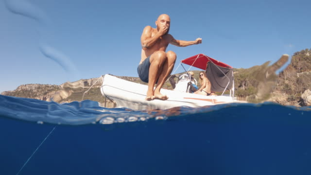video of a man jumping and diving in a summer sea from a boat - bomb stock videos & royalty-free footage