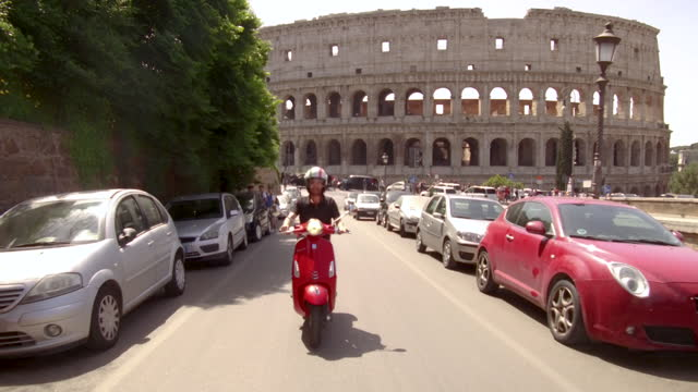 video of a man riding a red motorbike around the neighborhood of monti in rome, italy, at daytime - history stock videos & royalty-free footage