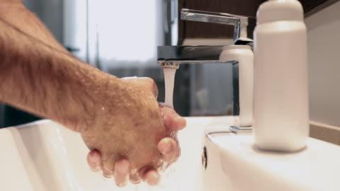 vídeos de stock, filmes e b-roll de vídeo 4k de um homem lavando as mãos no banheiro - lavar