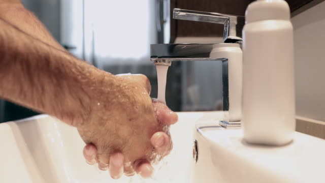 4k video of a man washing hands in bathroom - washing stock videos & royalty-free footage