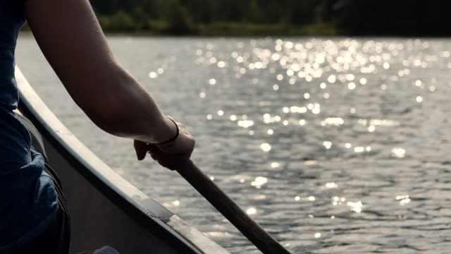 video of a portuguese woman canoeing on a lake at sunset. - pagaiare video stock e b–roll