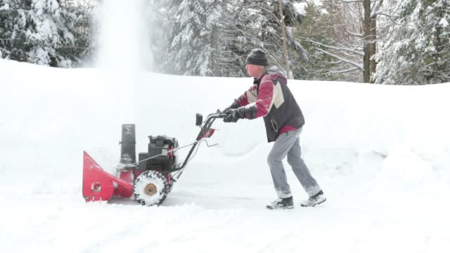 stockvideo's en b-roll-footage met 4k video van een senior man met behulp van sneeuwblazer na een sneeuwstorm - lepel