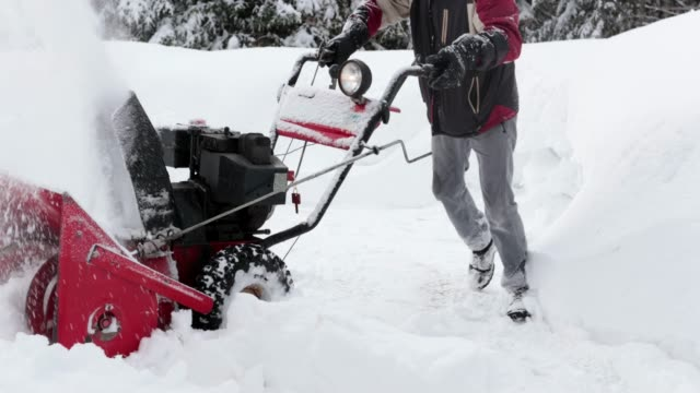 4k video of a senior man using snowblower after a snowstorm - snowplough stock videos & royalty-free footage