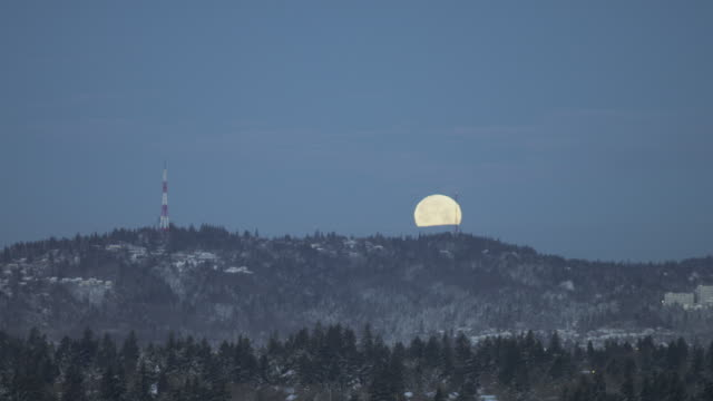 video of a wolf moon at dawn falling behind a snowy skyline with a city in the foreground - solstice stock videos & royalty-free footage