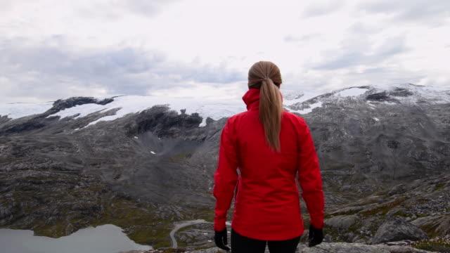 stockvideo's en b-roll-footage met video van een vrouw die op een rotsachtige berg wandelt. - mos plant